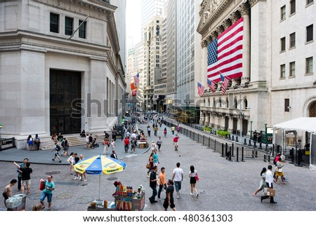 New York, NY: August 27, 2016: People walking by an American-flag draped New York Stock Exchange.   The NYSE is the world's largest stock exchange.