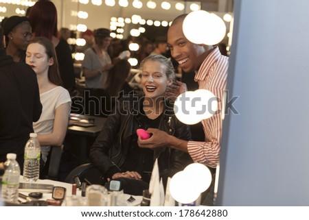 NEW YORK, NY - FEBRUARY 11, 2014: AJ Crimson applies skincare on model backstage for Australian Fashion Pallette presentation at Fall/Winter 2014 Fashion week at Pier 59 - stock photo