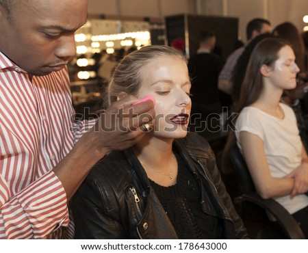 NEW YORK, NY - FEBRUARY 11, 2014: AJ Crimson applies skincare on model backstage for Australian Fashion Pallette presentation at Fall/Winter 2014 Fashion week at Pier 59