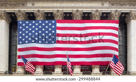 New York, NY - JULY 2015 - The New York Stock Exchange draped with a large American flag on Wall Street in New York City on July 19, 2015. - stock photo