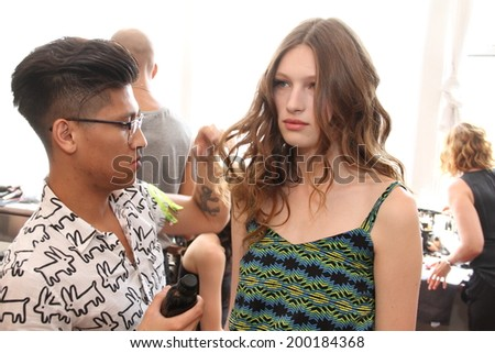 NEW YORK, NY - June 16: A hair stylist getting model ready backstage at the Claire Pettibone Spring 2015 Romantique Bridal collection show on June 16, 2014 in NYC.