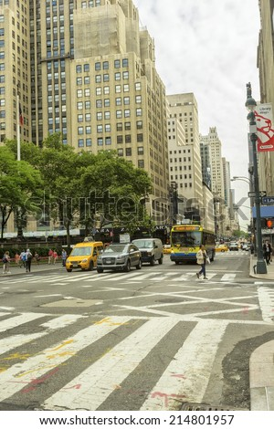 NEW YORK, NY - JUNE 23, 2014:  Midtown city street, near Fifth Avenue, in New York City.  Filled with pedestrians and traffic on a daily basis.