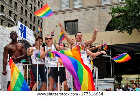 New York, NY- June 30, 2013:  Riders on the CUNY float waving rainbow flags at the annual Gay Pride parade on Fifth Avenue - stock photo