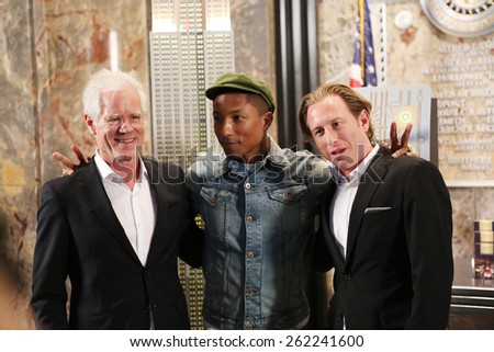 NEW YORK, NY - MARCH 20,2015: Pharrell Williams (C), Founder of Live Earth, Kevin Wall (L), and Aaron Grosky at The Empire State Building to mark United Nations International Day of Happiness - stock photo