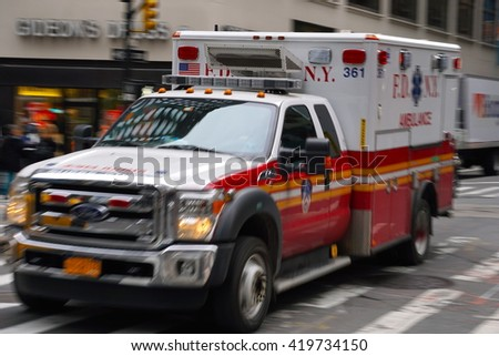 New York, NY - May 10, 2016: Long exposure motion blur of a FDNY ambulance speeding through busy Manhattan streets to give assistance in a medical emergency - stock photo
