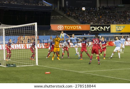 New York, NY - May 15, 2015: Sean Johnson of Chicago Fire (25), David Villa (7) & Patrick Mullins (14) of NYCFC fight for the ball during the game between NYCFC and Chicago Fire FC at Yankee Stadium - stock photo