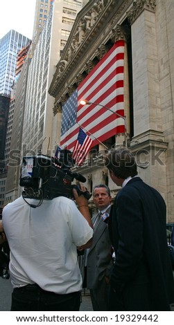 NEW YORK, NY -- OCTOBER 9, 2008: A news reporter interviews a stock trader outside of the New York Stock Exchange on October 9, 2008, the day the NYSE suffered its second greatest point drop ever