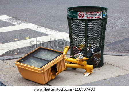 NEW YORK, NY - OCTOBER 31: Broken traffic light that fell during Hurricane Sandy lies discarded next to a trashcan in Lower Manhattan in New York, NY, on October 31, 2012. - stock photo
