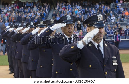 New York, NY - October 25, 2015: NYC police officers salute before match between NYC FC & New England Revolution at Yankee Stadium