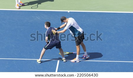 NEW YORK, NY - SEPTEMBER 7, 2014: Bryan brothers of USA play with ball boy during men doubles final match against Marcel Granollers & Marc Lopez of Spain at US Open championship in Flushing Meadows - stock photo