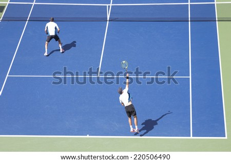 NEW YORK, NY - SEPTEMBER 7, 2014: Bryan brothers of USA serve ball during men doubles final match against Marcel Granollers & Marc Lopez of Spain at US Open championship in Flushing Meadows - stock photo