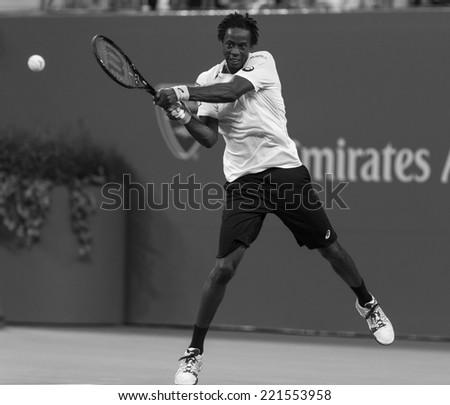 NEW YORK, NY - SEPTEMBER 4, 2014: Gael Monfils of France returns ball during quarterfinal match against Roger Federer of Switzerland at US Open championship in Flushing Meadows USTA Tennis Center - stock photo