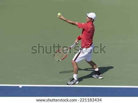 NEW YORK, NY - SEPTEMBER 6, 2014: Kei Nishikori of Japan serves ball during semifinal match against Novak Djokovic of Serbia at US Open championship in Flushing Meadows USTA Tennis Center - stock photo