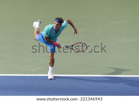 NEW YORK, NY - SEPTEMBER 6, 2014: Roger Federer of Switzerland serves ball during semifinal match against Marin Cilic of Croatia at US Open championship in Flushing Meadows USTA Tennis Center