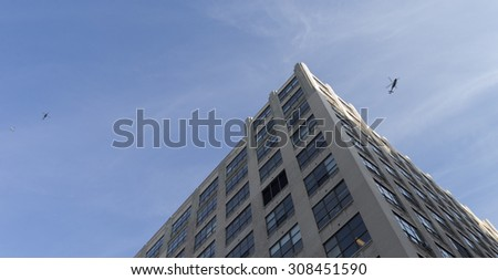 New York, NY USA - August 21, 2015: Police Helicopters flying above crime scene where security guard has been killed in Federal building on Varick street - stock photo