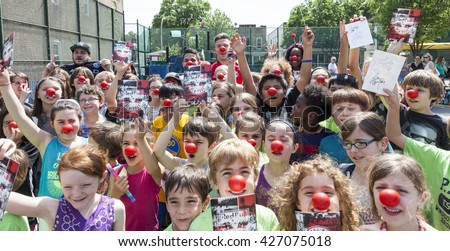 New York, NY, USA - May 26, 2016: New York Red Bull players Alex Muyl and Connor Lade celebrate 'Red Nose Day' with kids at the school yard of PS 154, Brooklyn - stock photo