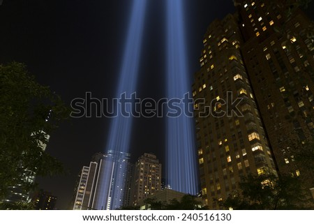 NEW YORK, NY USA - SEPTEMBER 11, 2014: Light tribute to World Trade Center 911 tragedy in downtown Manhattan with Freedom Tower on background - stock photo