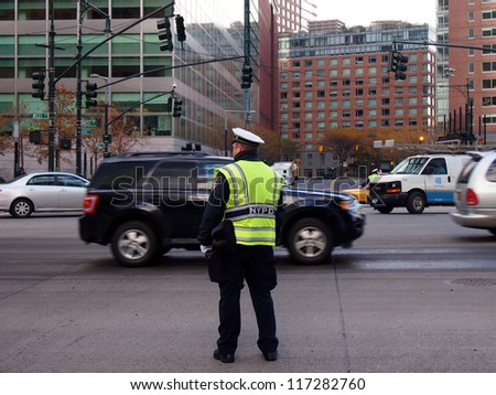 NEW YORK - OCT 31: A police officer directs traffic on West Street where a signal is out on October 31, 2012 in New York City, NY. Superstorm Sandy shut down much of the city. - stock photo