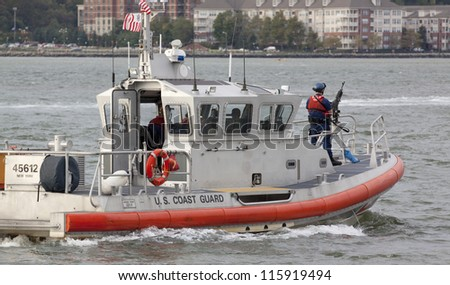 NEW YORK-OCT 6: Armed Coast Guard patrols the Hudson River near the USS Michael Murphy (DDG 112) docked at Pier 88 in New York on October 6, 2012. A formal ceremony commissioned the ship into service. - stock photo