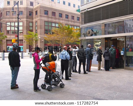 NEW YORK - OCT 31 2012: New Yorkers stand in a long line at a bagel shop in Battery Park City, New York City, NY. Superstorm Sandy shut down much of the city. - stock photo