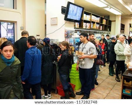 NEW YORK - OCT 30 2012: New Yorkers stand in a long line for coffee and supplies at one of the only open stores in Battery Park City, New York City, NY. Superstorm Sandy shut down much of the city. - stock photo