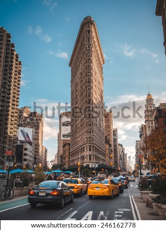 New york 11 OCT 2014 -NY taxi under The Flatiron Building. Finished in 1902, the landmark skyscraper was designated a City Landmark in 1966 and a National Historic Landmark in 1989.  - stock photo