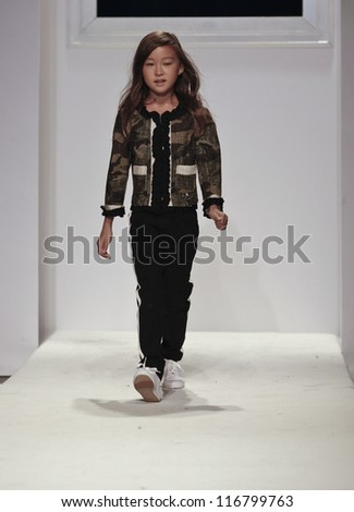 NEW YORK - OCTOBER 21: Girl walks runway for petite Parade show by Jakioo during kids fashion week sponsored by Vogue Bambini at Industria Superstudio on October 21, 2012 in New York City