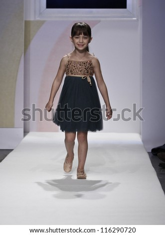 NEW YORK - OCTOBER 21: Girl walks runway petite Parade show by Lamantine Paris during kids fashion week sponsored by Vogue Bambini & Swarovski Elements at Industria Supertudio on Oct 21, 2012 in NYC - stock photo