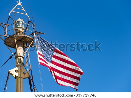 New York Port scenes: US Flag flying high on the crow nest of a sail ship, against a clear blue sky. The crow nest has a beacon fixed in it.
