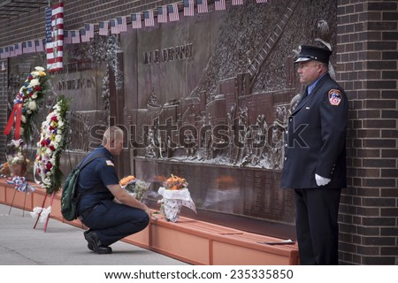 NEW YORK - SEPT 11, 2014: A firefighter pays his respects at the Memorial Wall at FDNY Engine 10 Ladder 10 House on Liberty St . The firehouse is directly across from the WTC site.  - stock photo