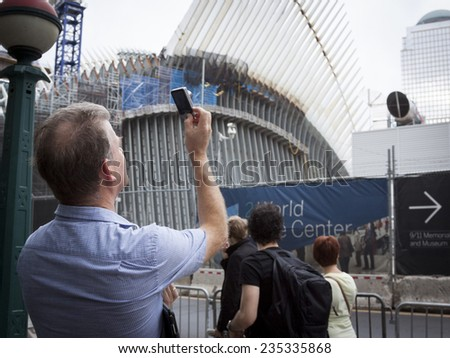 NEW YORK - SEPT 11, 2014: A man takes a picture of the Freedom Tower and structures at the WTC site on the anniversary of the 2001 September 11 terrorist attacks in Lower Manhattan. - stock photo