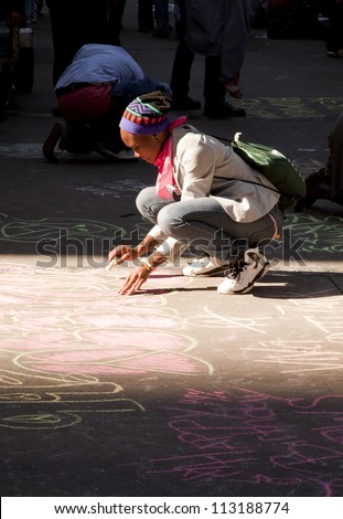 NEW YORK - SEPT 17: A protester writes on the sidewalk in front of Trinity Church with chalk on the 1yr anniversary of the Occupy Wall St protests on September 17, 2012 in New York City, NY.