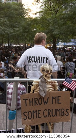 NEW YORK - SEPT 17: A security guard behind a sign that reads 'Throw Me Some Crumbs' in Zuccotti Park on the 1yr anniversary of the Occupy Wall St protests on September 17, 2012 in New York City, NY. - stock photo