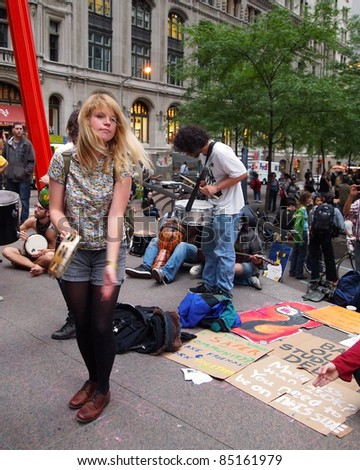 NEW YORK - SEPT. 21:A young woman plays tambourine amid the Occupy Wall Street demonstration near the New York Stock Exchange on September 21, 2011 in New York City - stock photo