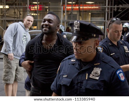 NEW YORK - SEPT 17: An unidentified man smiles as he is arrested on the 1yr anniversary of the Occupy Wall St protests on September 17, 2012 in New York City, NY. Attempts to elude police were futile. - stock photo