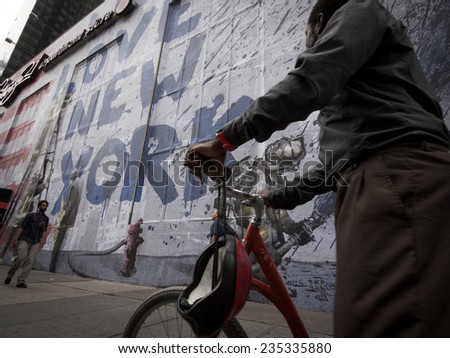 NEW YORK - SEPT 11, 2014: An unidentified man stops to look at the mural that says We Love New York featuring a firefighter spraying water from a hose on the anniversary of the 2001 terror attacks.