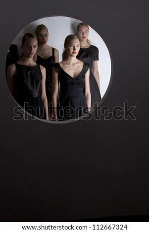 NEW YORK - SEPT 10: Models posing behind a round window opening at the bebeBLACK Spring/Summer 2013 collection during Mercedes-Benz Fashion Week in New York on September 10, 2012. - stock photo