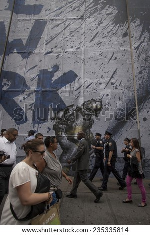 NEW YORK - SEPT 11, 2014: Tourists and business workers walk by a mural that says We Love New York featuring a firefighter spraying water from a hose on the anniversary of the 2001 terror attacks.