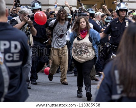 NEW YORK - SEPT 17: Two unidentified protesters being arrested on the 1yr anniversary of the Occupy Wall St protests on September 17, 2012 in New York City, NY. - stock photo