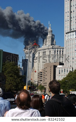 NEW YORK - SEPTEMBER 11 - Crowd witnesses South Tower of the World Trade Center collapsing as a result of terrorist attack while North Tower burns on September 11, 2001 at 9:59 am in New York. - stock photo