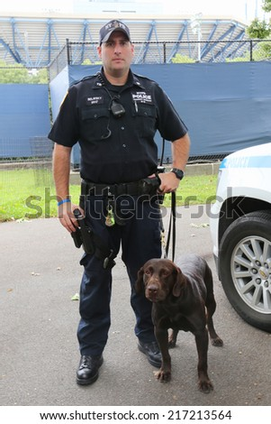 NEW YORK - SEPTEMBER 8: NYPD transit bureau K-9 police officer and Labrador K-9 Ellis providing security at National Tennis Center during US Open 2014 on September 8, 2014 in New York - stock photo