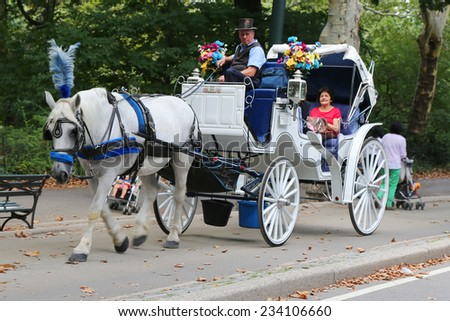 NEW YORK - SEPTEMBER 8: People enjoy carriage ride in Central Park on September 8, 2014 in Manhattan. Horse-Drawn Carriages are a wonderful way to experience the beauty of the Park - stock photo