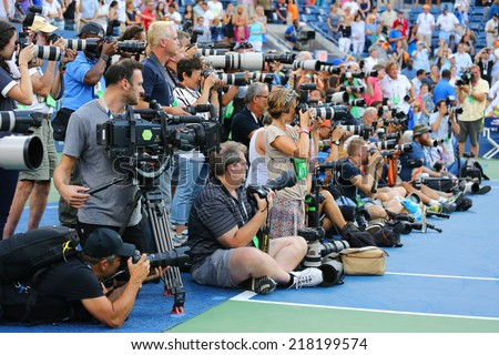 NEW YORK- SEPTEMBER 7 Professional photographers on tennis court during trophy presentation at the Arthur Ashe Stadium at Billie Jean King National Tennis Center on September 7, 2014 in New York - stock photo