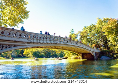 NEW YORK - SEPTEMBER 28: Rowboats in Central Park lake under the Bow Bridge on September 28, 2013, New York, NY. The 20-acre Lake is the second largest of Central Park's man-made water bodies.  - stock photo
