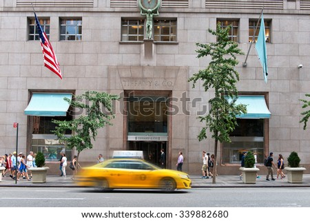 NEW YORK - SEPTEMBER 06: Yellow Taxi Cab Speeding Past Entrance to Tiffany and Company Luxury Jewellery Retail Store on Street Busy with Pedestrians in New York City, New York, USA. September 06 2015. - stock photo