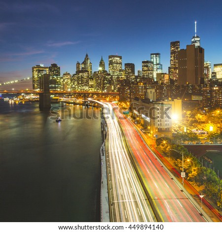New york skyline at night with Brooklyn bridge and light trails on the road. Long exposure from Manhattan bridge with downtown skyscrapers on background. - stock photo