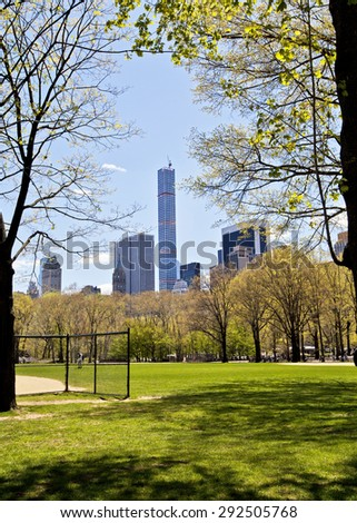 New York skyline seen from the baseball fields of Central Park through the trees - stock photo