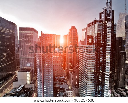 New York skyscrapers above Times Square at dawn with added sunlight effect - stock photo