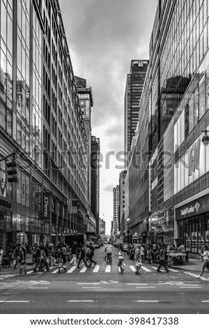 New York, United Stated of America - September 20, 2015: People crossing W33rd Street on the Avenue of the America's, or Sixth Avenue, in Manhattan on a September evening in 2015 in black and white - stock photo