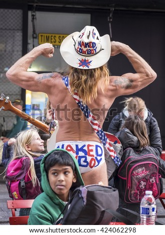 NEW YORK, UNITED STATES - NOVEMBER 1, 2015: The Naked Cowboy poses with flexed biceps in Times Square for a photograph.